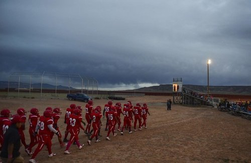 The Red Mesa (Ariz.) High School football team approaches the field before its homecoming game against Many Farms High School on Oct. 17.