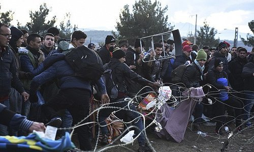 Migrants storming Greek-Macedonian border fence Nov. 26, 2015.