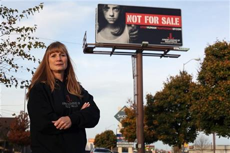 Dawn Stenberg, from the Junior League of Sioux Falls, stands near the group's anti-human trafficking billboard in Sioux Falls, S.D.