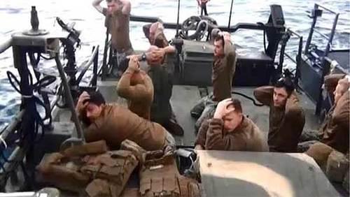 U.s. sailors kneeling on the deck of their patrol boat
