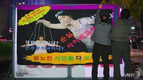 Protestors hang a caricature showing south korean president park